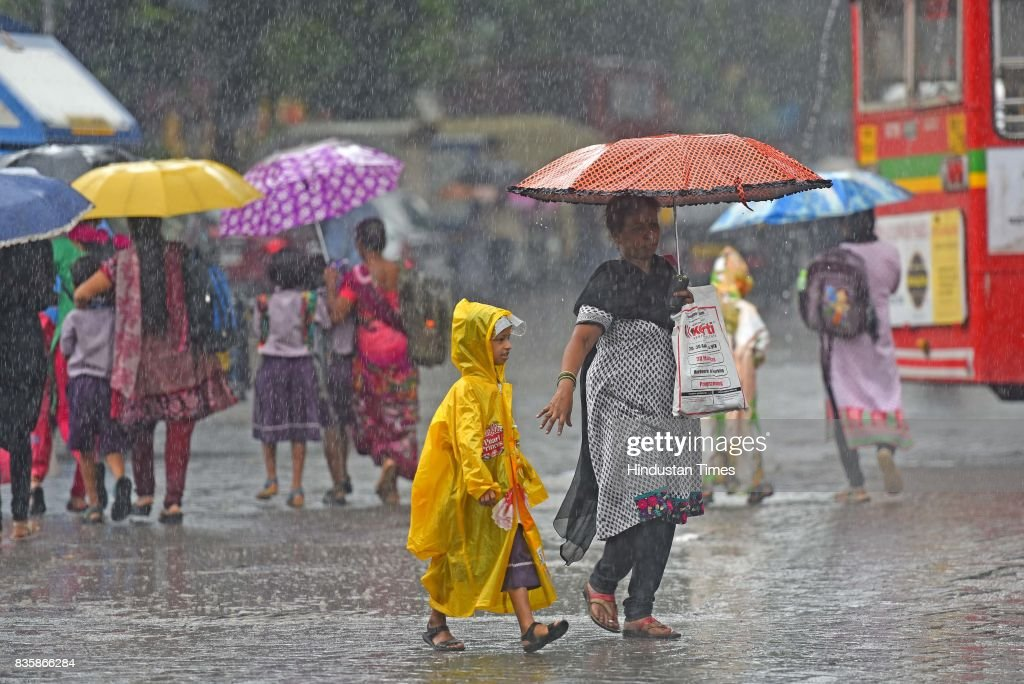 People stuck during the rain at Parel, on August 19, 2017 in Mumbai, India. These weather conditions have been attributed to the presence of a low pressure which is currently lying over the Vidarbha region. Due to this, moisture incursion has increased over Mumbai as well as Thane and the cities have recorded these heavy spells.
