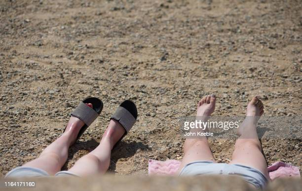 People sunbath and get sore feet on the beach on July 25 2019 in SouthendonSea United Kingdom The Met Office issued a weather warning from 3pm this...