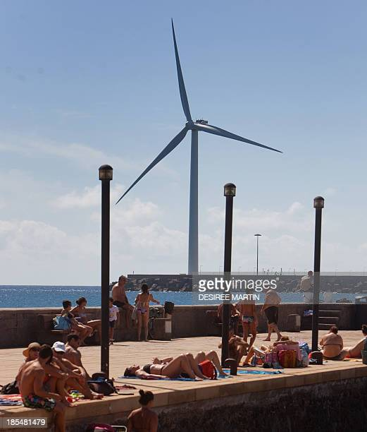 People sunbath backdropped by Spain's largest wind turbine Arinaga a five megawatts turbine standing 154 metres with 625metre long blades at the end...
