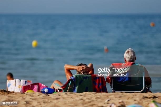 People sunbath in CollevilleMontgomery northwestern France on July 6 2018