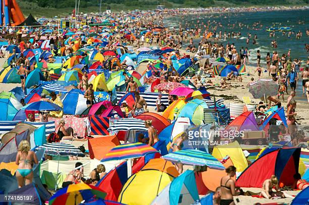 People sunbath on a beach o the Baltic sea on July 21, 2013 in Zinnowitz, Germany. AFP PHOTO / DPA /STEFAN SAUER /GERMANY OUT
