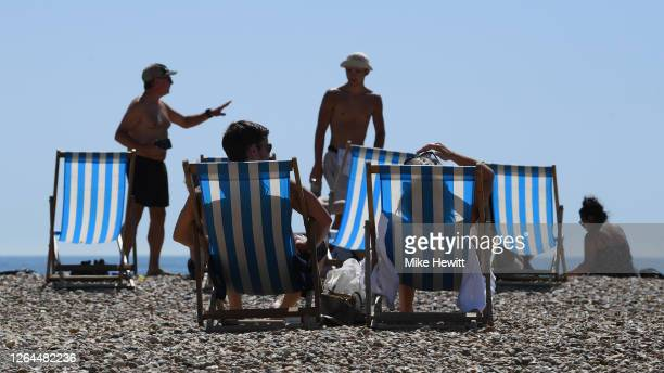 People sunbath on Brighton beach as the South of England basks in a summer heatwave on August 07, 2020 in Brighton, United Kingdom. Parts of England...
