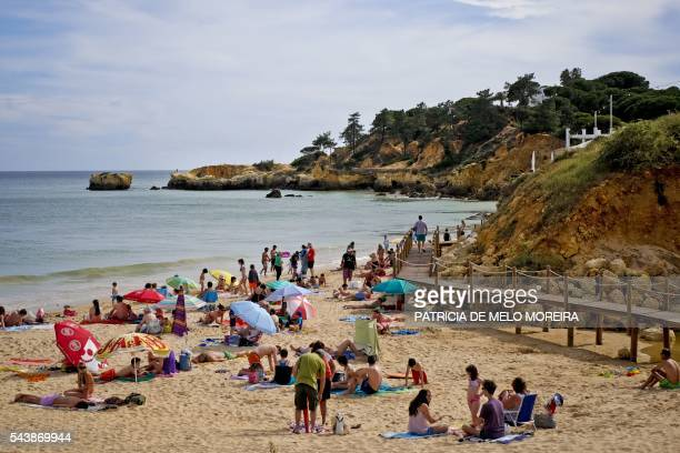 People sunbath on Santa Eulalia beach at Albufeira Loule southern Portugal on June 10 2016 Instability and violence in the Mediterranean's former top...