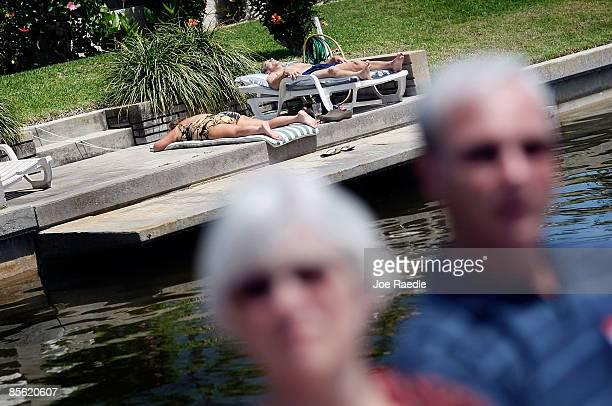 People sunbath on their dock as Susan Crow and Tom Crow along with other prospective buyers float past as they take part in a foreclosure boat tour...