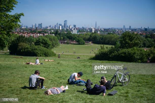 People sunbathe and socialise on Parliament Hill on May 29 2020 in London England From Monday groups of up to six people from different households...