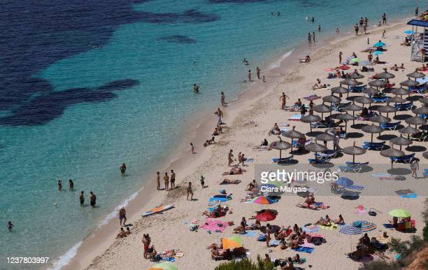 People sunbathe and swim in Portals Nous beach in the island's municipality of Calvia on May 31, 2020 in Mallorca, Spain. All regions of Spain have...