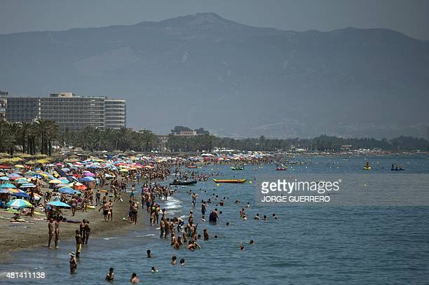 People sunbathe and swim on the beach of Torremolinos on July 20 2015 In Spain started on July 20 2015 a new heatwave Spain is preparing for the...