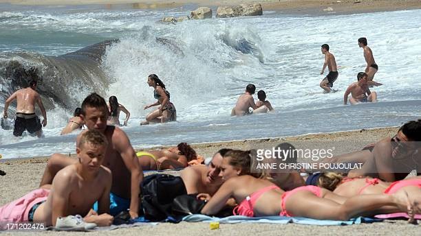 People sunbathe as a strong mistral wind blows on Prado beach in Marseille southern France on June 23 2013