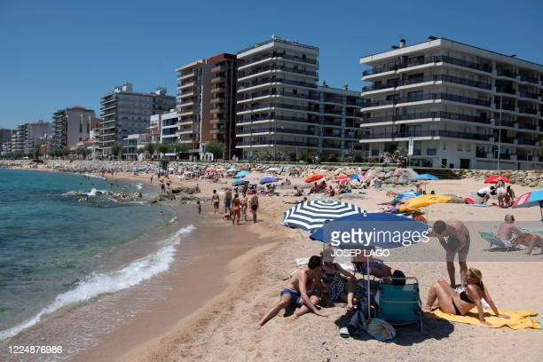 People sunbathe as they enjoy a day out at the beach in Platja DAro near Girona on July 5 2020 Spaniards endured one of the world's toughest...