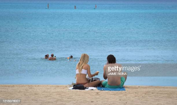 People sunbathe at Palma Beach in Palma de Mallorca on May 25 on the first day after beaches reopened in parts of the country after monthslong...