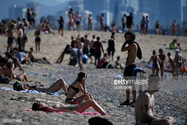 People sunbathe at the Barceloneta beach in Barcelona on May 20, 2020 during the hours allowed by the government to exercise, amid the national...
