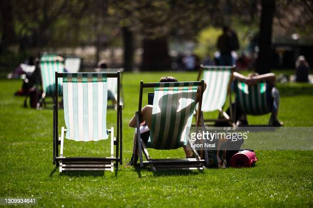 People sunbathe in St James' Park as the temperature hits an unusually high on March 30, 2021 in London , England. Despite todays temperature heading...