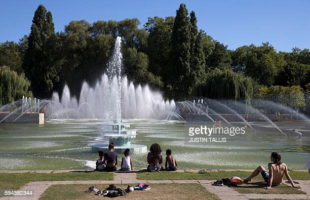 People sunbathe next to water fountains in Battersea Park in London on August 23 as blue skies and warm temperatures sweep the capital / AFP / JUSTIN...