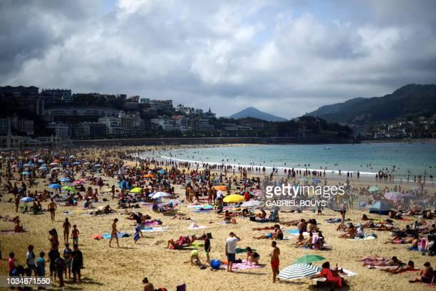 People sunbathe on a sunny day at La Concha beach in the Spanish Basque city of San Sebastian on September 16 2018