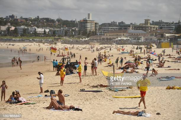 People sunbathe on Bondi Beach ahead of its closure in Sydney on March 21 2020 Authorities temporarily closed Bondi Beach on March 21 after huge...
