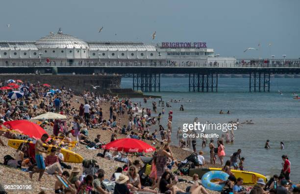 People sunbathe on Brighton beach as the sun is out before dark storm clouds began to form over the city on May 28 2018 in Brighton England A yellow...