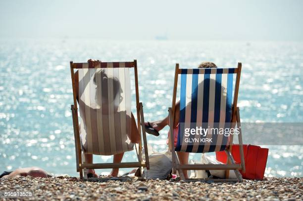 People sunbathe on Brighton Beach southern England on August 26 2016 Five beachgoers on Camber Sands beach on the south coast died as Britain...