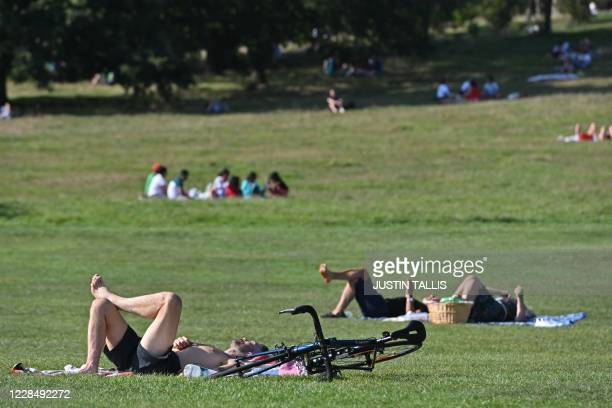 People sunbathe on Primrose Hill in central London in the late summer sunshine on September 13 the day before the UK government brings in tightened...