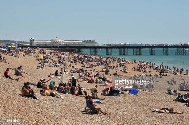 People sunbathe on the beach and cool off in the sea in Brighton on the south coast of England on May 31 2020 on the eve of a further relaxation of...