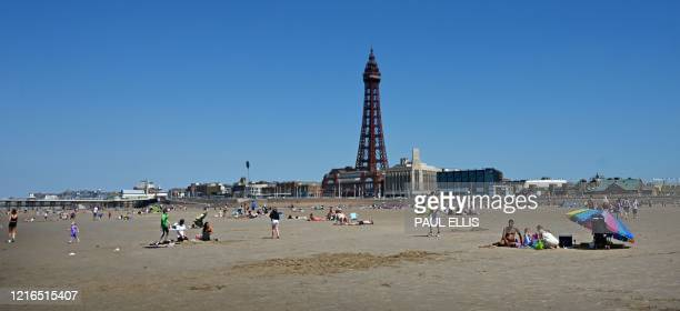 People sunbathe on the beach in Blackpool on the north-west coast of England on May 31, 2020 on the eve of a further relaxation of the novel...