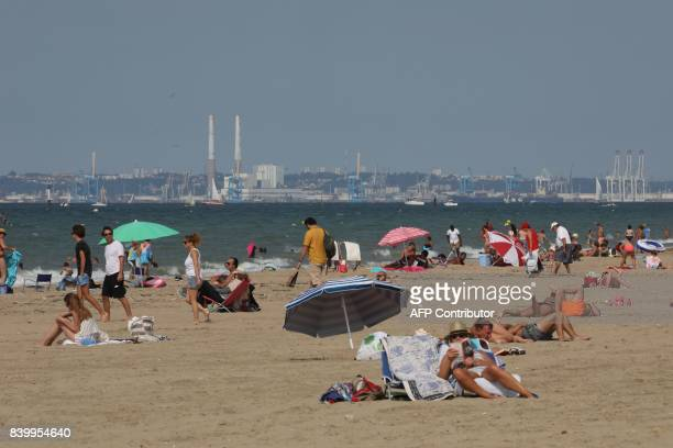 People sunbathe on the beach in Deauville western France on August 27 as the city of Le Havre is seen in the backround / AFP PHOTO / ludovic MARIN