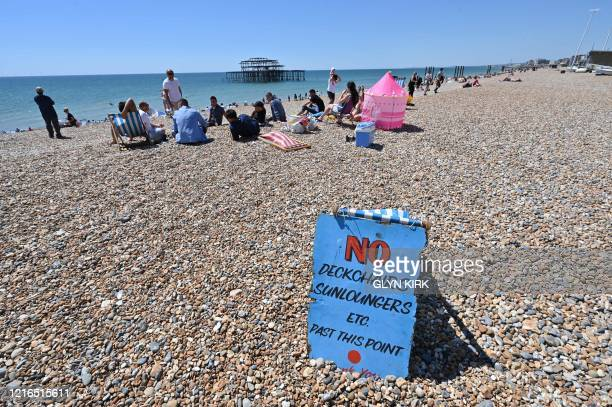 TOPSHOT People sunbathe on the beach in front of the derelict West Pier in Brighton on the south coast of England on May 31 2020 on the eve of a...