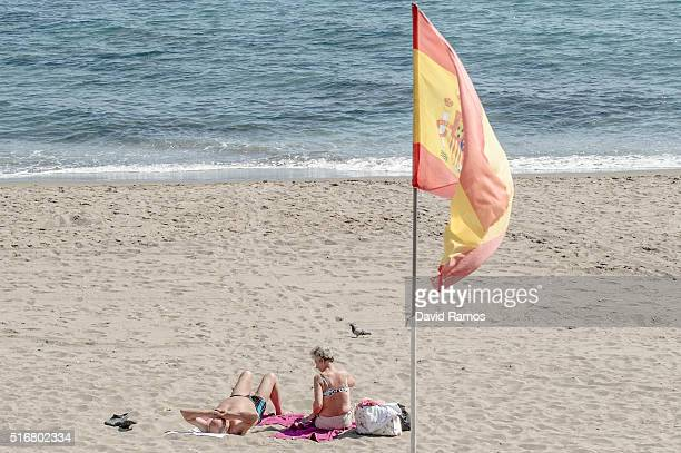 People sunbathe on the beach near a Spanish flag on March 17 2016 in Benalmadena Spain Spain is Europe's top destination for British expats with the...