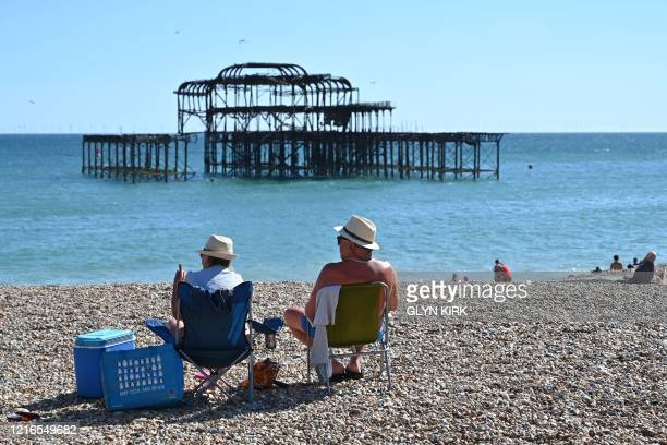 People sunbathe on the beach near the derelict West Pier in Brighton on the south coast of England on May 31, 2020 on the eve of a further relaxation...