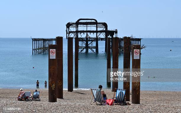 People sunbathe on the beach near the derelict West Pier in Brighton on the south coast of England on June 2, 2020 following a further relaxation of...