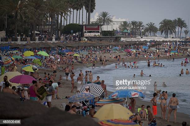 People sunbathe on the beach of Marbella on August 9 2015 AFP PHOTO/ JORGE GUERRERO