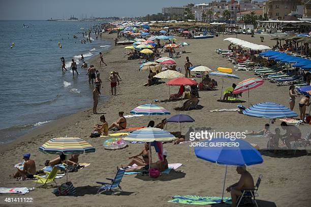 People sunbathe on the beach of Torremolinos on July 20 2015 In Spain started on July 20 2015 a new heatwave Spain is preparing for the third...