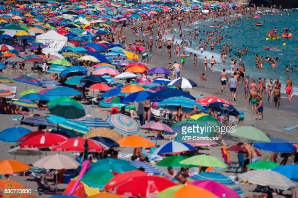 People sunbathe on the Burriana beach in Nerja near Malaga on August 12 2017 / AFP PHOTO / JORGE GUERRERO