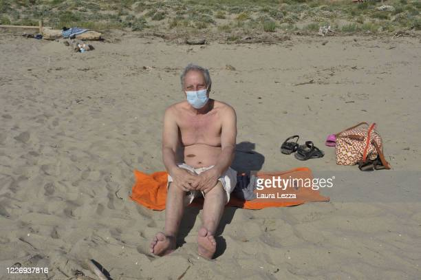 People sunbathe with social distance and protective mask on the free beach near Pisa on May 25 2020 in Pisa Italy From 18 May access to the sea is...