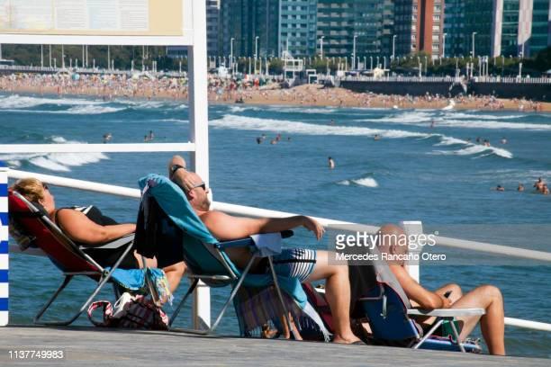 People sunbathing, cityscape and San Lorenzo beach from pedestrian walkway in Gijón, Spain
