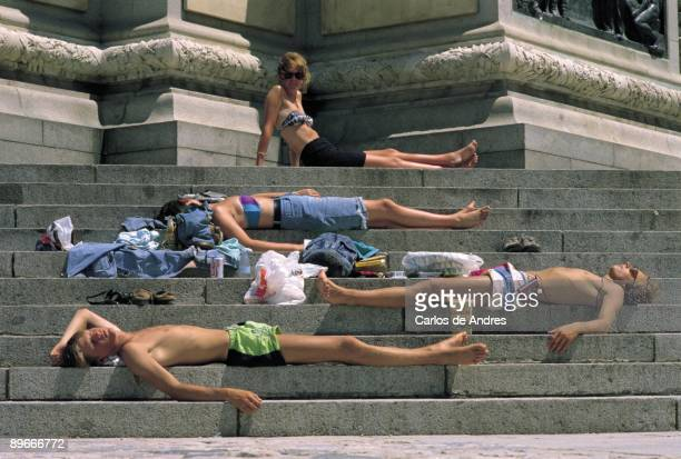 People sunbathing on a stairways Tourists sunbathing and sleeping on the stairways of a monument in a city