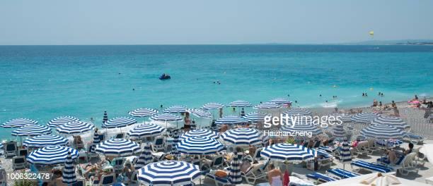 mensen zonnebaden op het strand in nice, frankrijk - nice frankrijk stockfoto's en -beelden