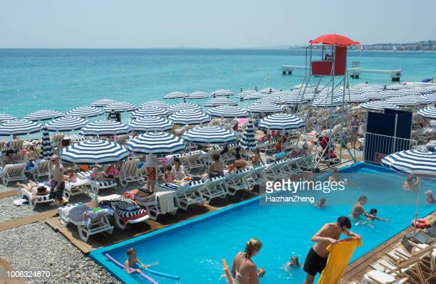 people sunbathing on the beach in nice, france - herpes zoster foto e immagini stock