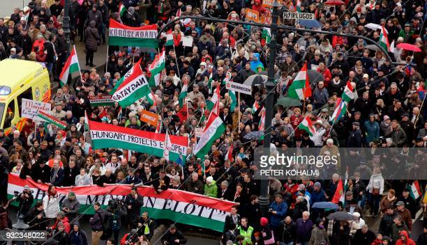 People supporting the government of Hungary's Prime Minister carry flags in the colors of their country as they take part in a Peace March in...