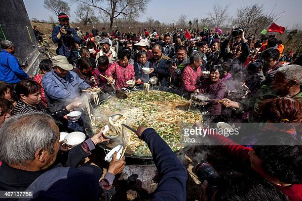 People surround a cauldron to eat noodles at Bailongtan Temple Fair on March 21 2015 in Anyang Henan province of China Each year on Dragon...