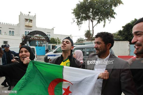People surround Idir Ali as he holds an Algerian national flag after being acquitted by an Algerian tribunal, in the capital Algiers on November 13,...