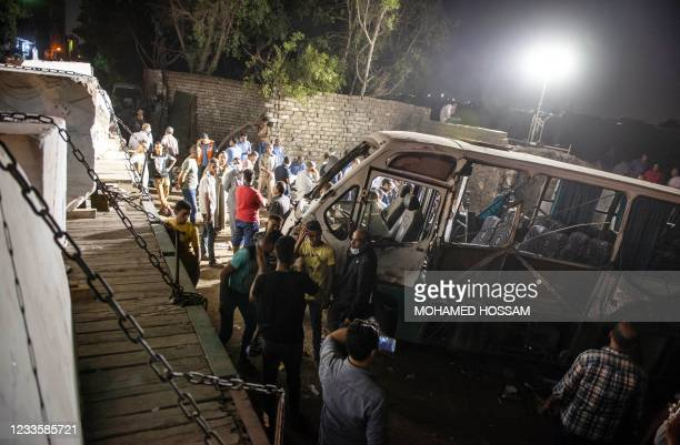 People surround one mini-bus after it collided with a cargo train, on June 21 2021 in the southern of the Egyptian capital Cairo. - Two people killed...