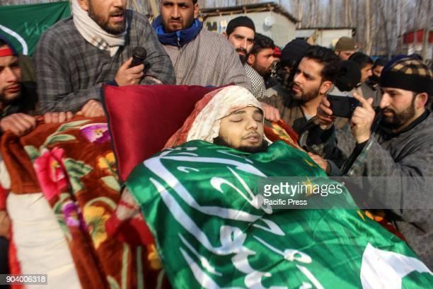 People surround the body of a 16 year old Kashmiri rebel Farhan Ahmad Wani during his funeral at Redwani village of Kulgam District