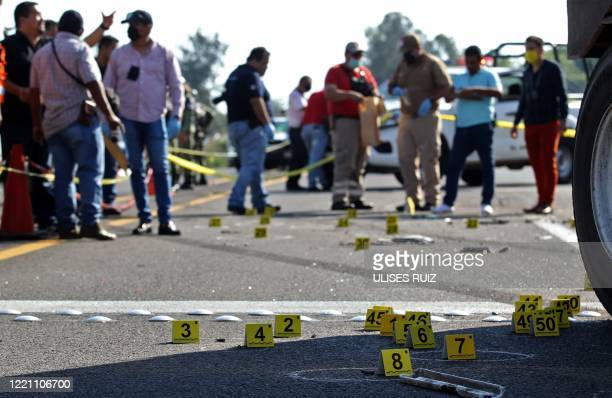 People surround the site where a security transport truck was ambushed by an armed group who killed four private guards in an assault on the...