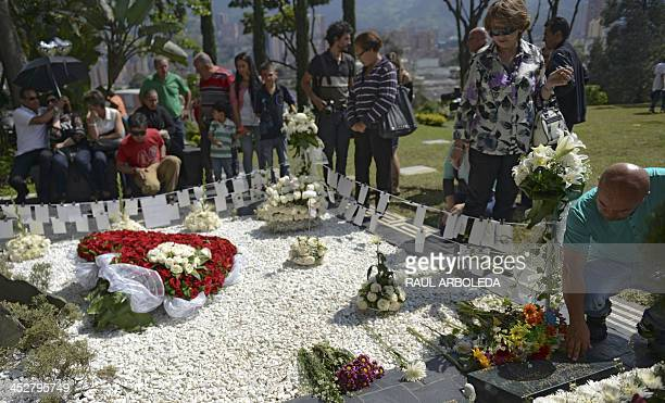 People surround the tomb of Colombian drug lord Pablo Escobar at Montesacro cemetery in Medellin, Antioquia department, Colombia on December 1 a day...