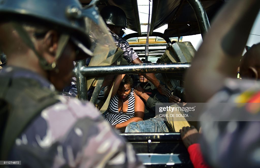 TOPSHOT - People suspected of being involved in protests sit in the back of a vehicle after being arrested by police in Kampala on February 19, 2016 during the presidential election vote. Voting was extended in 36 sites for a second day after delays on February 18 that Commonwealth election observers called 'inexcusable'. Some frustrated voters accused the authorities of deliberately stalling the vote. Ugandan President Yoweri Museveni is widely predicted to win a fifth term. / AFP / CARL