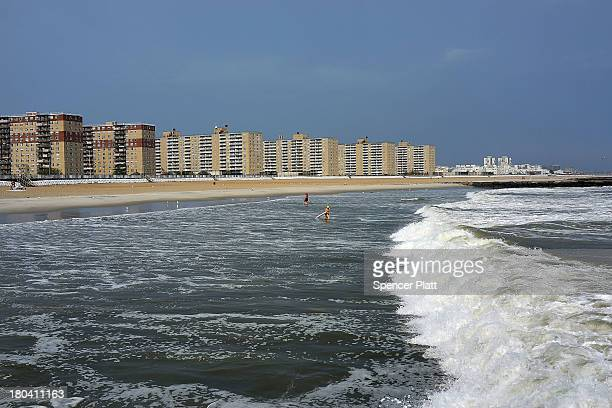 People swim along a largely empty Rockaway Beach on September 12, 2013 in the Queens borough of New York City. Despite the sustained damage in the...