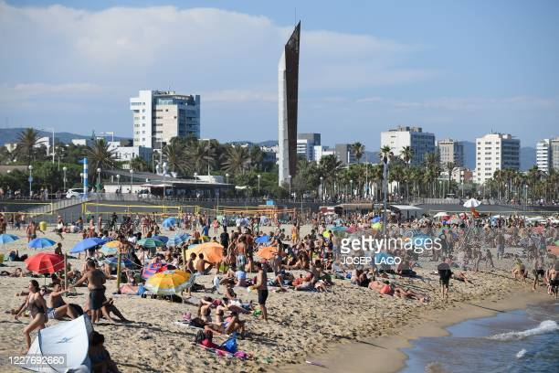 People swim and sunbathe at the Bogatell beach in Barcelona one of the several sands of the city that have been closed on July 19 2020 due to...