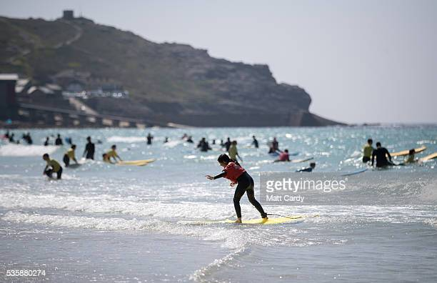 People swim and surf in the sea as they enjoy the fine weather as they gather on the beach at Sennen Cove on May 30 2016 in Cornwall England As some...