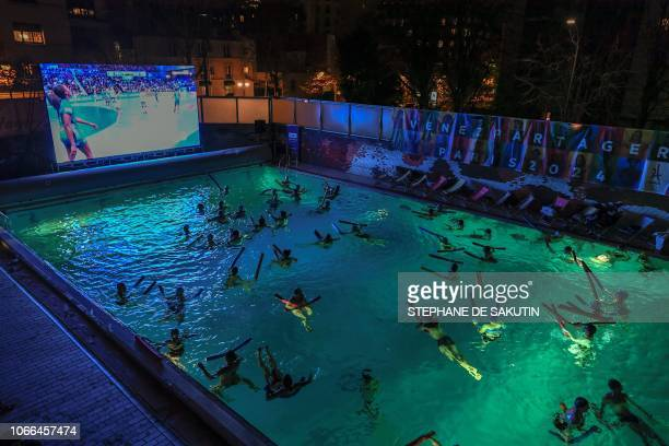 People swim as they watch on a giant screen the preliminary tour of the group B of the Euro 2018 Championship handball match between France and...
