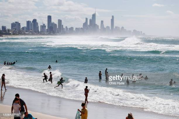 People swim at Burleigh Heads beach on May 16, 2020 in Gold Coast, Australia. Restrictions have eased across Queensland under Stage 1 of the state...
